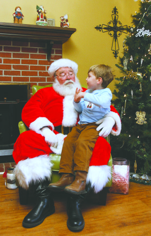 Sitting in Santa's lap: Three-year-old Parker Kuhn takes time to visit with Santa during the Hope Landing Christmas at the Ranch event.