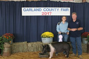 Submitted photo RESERVE GRAND CHAMPION MARKET HOG: The hog of Bailey Helton, left, won the title of Reserve Grand Champion Market Hog. Buyer was American Termite and Pest Control, represented by Bobby Adcock.