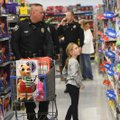 Cpl. Kenneth Trimberger with the Bentonville Police Department helps Tori Creekmore, 8, select Chris...