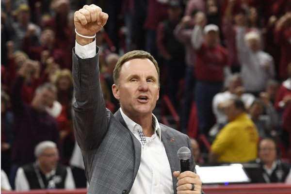 Chad Morris, the new University of Arkansas head football coach, calls the hogs with fans as he is introduced during the first half of an NCAA college basketball game Saturday, Dec. 9, 2017 in Fayetteville, Ark. (AP Photo/Michael Woods)