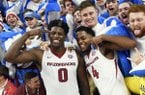 Arkansas players Jaylen Barford (0) and Daryl Macon (4) celebrate with fans after beating Minnesota after the second half of an NCAA college basketball game Friday, Dec. 9, 2017 in Fayetteville, Ark. (AP Photo/Michael Woods)