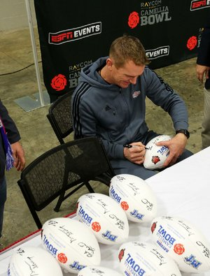 Arkansas State Coach Blake Anderson signs commemorative Camellia Bowl footballs Friday in Montgomery, Ala. The Red Wolves take on Middle Tennessee State tonight.