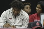 Fordyce High School senior Billy Ferrell (left) signs a letter of intent to play football at the University of Arkansas on Wednesday, Dec. 20, 2017, in Fordyce. Joining Ferrell was his mother Rene Stuckey (right) and younger brother, Malik Harden (center).