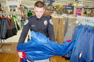 Graham Thomas/Siloam Sunday Siloam Springs Police officer Zachary Ware helps 10-year-old Aaron Engleman try on a hooded sweatshirt during the Cops and Kids event held Wednesday at Walmart Supercenter in Siloam Springs.