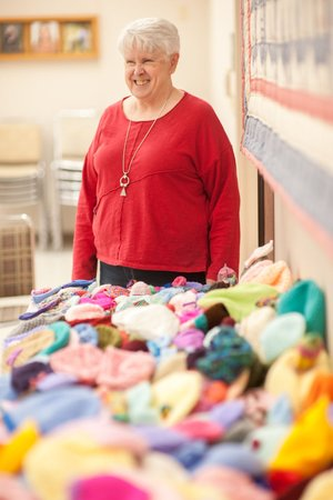 NWA Democrat-Gazette/LARA JO HIGHTOWER Betty Johnson of Springdale stands behind the 300 kitted and crocheted hats she made to be worn by babies and children at the new Arkansas Children's Northwest children's hospital in Springdale. The project took her just about a year.