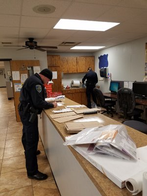 NWA Democrat-Gazette/ASHTON ELY Cpl. Marcus Peace and Officer Seay Floyd work to sort through some of the mail that was scattered during Tuesday night's mail thefts across east Fayetteville.