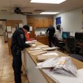 Cpl. Marcus Peace and Officer Seay Floyd work to sort through some of the mail that was scattered du...