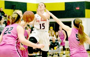 RICK PECK/SPECIAL TO MCDONALD COUNTY PRESS McDonald County's Ragan Wilson goes in for a layup as Neosho's Caitlyn Johnson (22) and Mary Dunbar (5) look on during the Lady Mustangs' 54-30 loss on Dec. 28 in the opening round of the 63rd Neosho Holiday Classic.