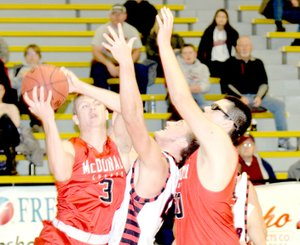 RICK PECK/SPECIAL TO MCDONALD COUNTY PRESS McDonald County's Peyton Barton grabs a rebound away from Lamar's Travis Bailey as Tim Shields puts Bailey in a Mustang vice during McDonald County's 64-57 win on Dec. 30 in the 13th-place game of the 63rd Neosho Holiday Classic.