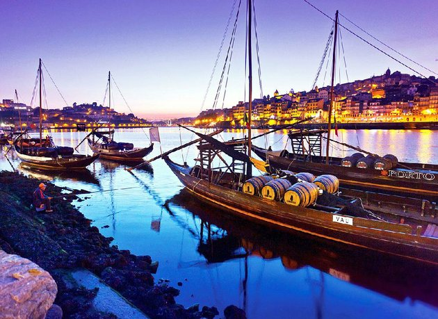 traditional-rabelo-boats-which-were-once-used-to-deliver-port-wine-from-the-douro-valley-line-portos-harbor-at-sunset