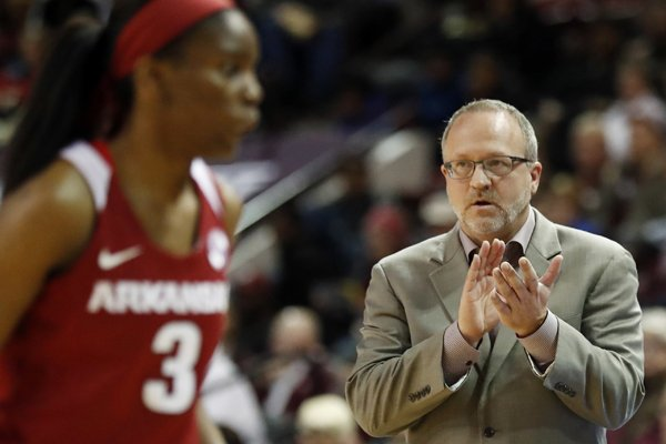 Arkansas coach Mike Neighbors applauds his players as a timeout is called in the first half of an NCAA college basketball game against Mississippi State in Starkville, Miss., Thursday, Jan. 4, 2018. Mississippi State won 111-69. (AP Photo/Rogelio V. Solis)