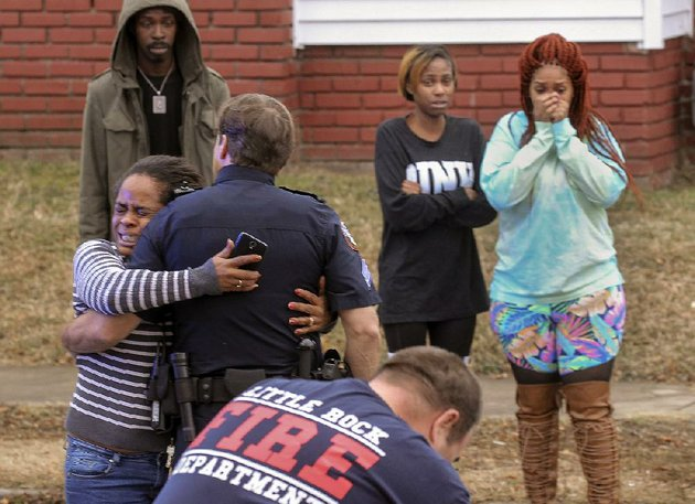 an-upset-woman-is-held-back-by-police-as-firefighters-and-paramedics-try-to-revive-a-man-fatally-shot-monday-afternoon-in-little-rock-the-man-was-shot-at-eastview-terrace-apartments-on-east-13th-and-geyer-streets-and-was-then-driven-a-few-blocks-away-to-east-15th-and-college-streets-where-he-was-administered-cpr-by-rescue-workers
