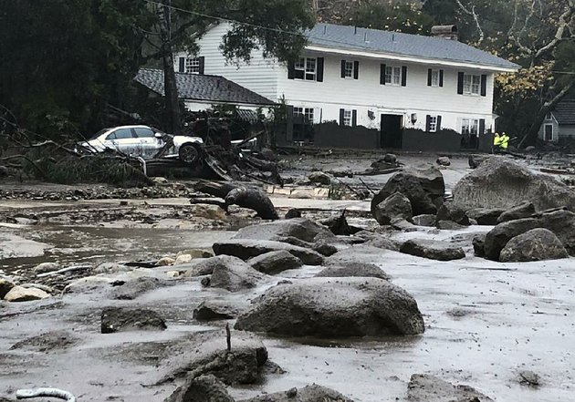 rocks-mud-and-debris-cover-a-street-in-montecito-calif-on-tuesday-marks-on-the-house-in-the-background-show-how-high-the-mud-rose-as-it-swept-through-the-neighborhood