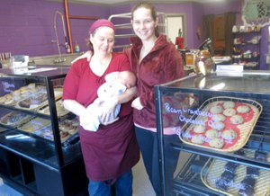 Westside Eagle Observer/SUSAN HOLLAND Maria Dolberry, her daughter Deborah Barber and granddaughter Lilith posed recently beside the display cases filled with baked goods at their Dessert Diversity shop in Sulphur Springs. The business is open 6:30 a.m. to 6:30 p.m. Mondays, Tuesdays, Thursdays and Fridays and 8 a.m. to 3 p.m. Saturdays and Sundays. Telephone number for the bakery is 479-298-1233.