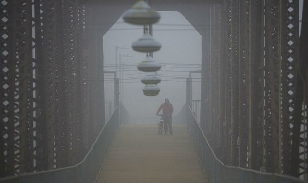 fredrick-williams-jr-walks-across-the-clinton-presidential-center-bridge-on-wednesday-afternoon-as-fog-shrouds-the-arkansas-river