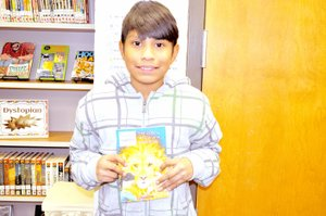 "RACHEL DICKERSON/MCDONALD COUNTY PRESS Christian Rubio, fifth-grader at Noel Elementary, is pictured with ""The Lion, the Witch and the Wardrobe,"" the book for this year's One Book, One County countywide read-along."