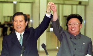 FILE -- In this June 14, 2000, file photo, South Korean President Kim Dae-jung, left, and North Korean leader Kim Jong Il raise their arms together before signing a joint declaration during a summit in Pyongyang, North Korea. Leaders of the two Koreas have met only twice for summit talks during the last 70 years, and talks of a third summit flared again Wednesday, when the south's current liberal President Moon Jae-in said he's willing to meet North Korean leader Kim Jong Un if the success of the meeting is guaranteed. (Yonhap Pool Photo via AP, File)
