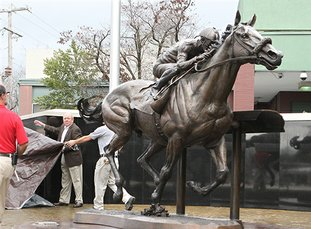 The Sentinel-Record/Richard Rasmussen WINNER'S CIRCLE: Oaklawn Park employees unveil a bronze sculpture of Triple Crown winner American Pharoah on Thursday during the official ribbon-cutting ceremony.