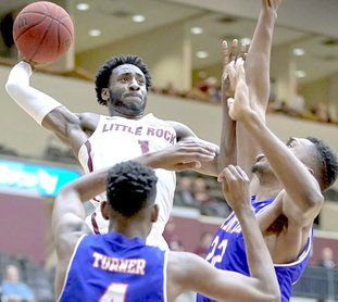 Submitted photo WITH AUTHORITY: Sophomore guard Andre Jones (1), a graduate of Malvern, rises for a score over UT-Arlington defenders Davion Turner (4) and Link Kabadyundi (22) Thursday at the Jack Stephens Center in Little Rock. Jones scored 24 points to help the Trojans win 77-65.
