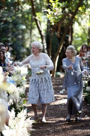 """Nancy """"Grongong"""" Rutchik (left) and Flossie """"Grammy"""" Pack, walk down the aisle as flower girls for the wedding of their granddaughter Lucy Schanzer in Carmel, Calif., in 2015. Lucy married Kyle Schanzer."""