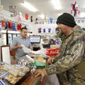 Dale Hunt (right), of Winslow, waits at the counter Friday to purchase merchandise and cash his payc...