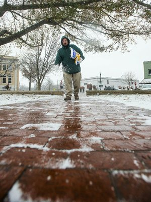 Chris Kester with the Bentonville Parks and Recreation Department spreads salt on the sidewalks Monday around the Bentonville square.