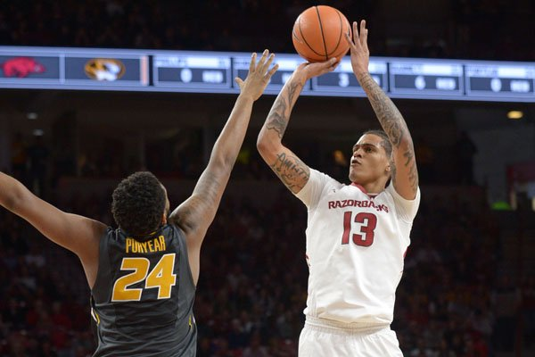 Arkansas forward Dustin Thomas shoots over the top of Missouri forward Kevin Puryear during a game Saturday, Jan. 13, 2018, in Fayetteville.