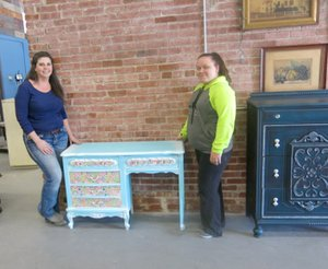 WESTSIDE EAGLE OBSERVER/Susan Holland Dawn Dawson (left), owner of White Horse Designs by Dawn, and her partner, Aubrey Doss, display a dressing table they recently refinished at her workshop at 104 Main Street N.E. in Gravette. The piece was painted and powder glazed in pastel colors in preparation for use in a teenage girl's bedroom. The ladies invite area residents to contact them with any furniture refinishing or restoration projects they want done.