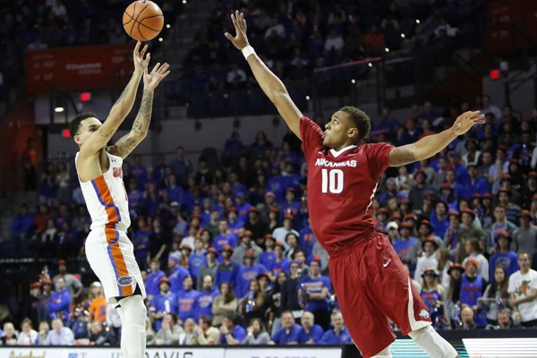 Florida guard Chris Chiozza (11) goes up for a 3-point shot against an Arkansas defender during an NCAA college basketball game in Gainesville, Fla., Wednesday Jan. 17, 2018. Florida won, 88-73. (Brad McClenny/The Gainesville Sun via AP)