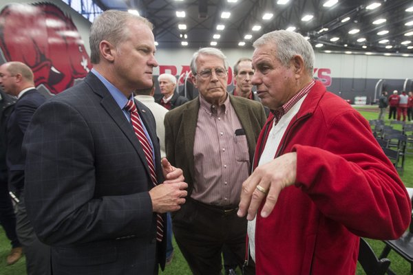 Former Arkansas coach Ken Hatfield, right, speaks with Arkansas athletic director Hunter Yurachek, left, and A Club president Dick Hatfield following a news conference Thursday, Dec. 7, 2017, in Fayetteville.
