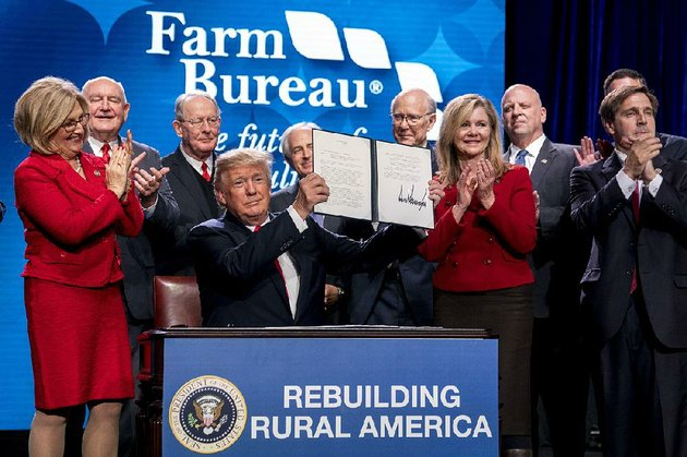 president-donald-trump-holds-up-a-signed-executive-order-and-a-memorandum-on-rural-broadband-access-at-the-american-farm-bureau-federations-annual-convention-jan-8-in-nashville-tenn