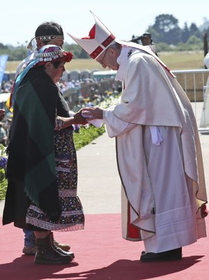 A Mapuche woman greets Pope Francis during the offertory during a Mass at the Maquehue Air Base, in Temuco, Chile, Wednesday, Jan. 17, 2018. Francis is urging the Mapuche people to reject violence in pushing their cause. Francis made the comments Wednesday while celebrating Mass in Temuco. The city is the capital of the Araucania region, where many of Chile's estimated 1 million people of Mapuche descent live. (AP Photo/Alessandra Tarantino)