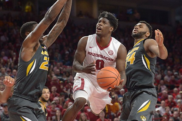 Arkansas guard Jaylen Barford (0) drives to the basket as he is pressured by Missouri forward Jeremiah Tilmon (left) Saturday, Jan. 13, 2018, during the second half in Bud Walton Arena.