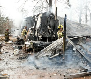 The Sentinel Record/Richard Rasmussen TRAILER ENGULFED: Members of the Lonsdale and Morning Star fire departments extinguish a trailer house fire at 354 Rigsby Loop on Friday. Eight firefighters from each department responded to the fully engulfed fire around 9 a.m. and had the flames controlled in less than 15 minutes. The probable cause was attributed to a wood stove fire which resulted in the total loss of the structure and belongings.