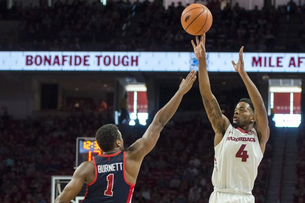 Arkansas Razorbacks guard Daryl Macon (4) shoots a three as Mississippi Rebels guard Deandre Burnett (1) covers during a basketball game, Saturday, January 20, 2018 at Bud Walton Arena in Fayetteville.