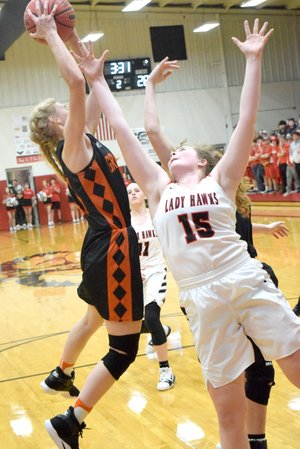 Westside Eagle Observer/MIKE ECKELS Jessica Bookout (Lady Lions 23) grabs a rebound away from Maria Socha (Lady Hawks 15) during the second quarter of the Pea Ridge-Gravette senior girls basketball contest at Blackhawk Gym in Pea Ridge Jan.19. The Lady Lions defeated the Lady Hawks 58-56.