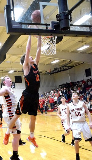 Westside Eagle Observer/MIKE ECKELS After a fast break from midcourt, Kelton Trembly (Gravette 12) goes high for a dunk during the second half of the Pea Ridge-Gravette senior boys' basketball contest at Blackhawk Gym in Pea Ridge Jan. 19.