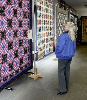 Westside Eagle Observer/RANDY MOLL Sandy Brandon looks at quilts on display during the Gentry Chamber of Commerce quilt show held at the Gentry Public Library last week.