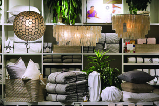 Lamps from the Philippines, made of seashells, hang over a display of artisanal items, at a West Elm store in New York. On the lower shelf are: a basket from India, left; paper mache vases from Haiti, center; and pillows from India, right. There have been growing initiatives to help artisans from some of the poorest global regions gain access to the U.S. market to spur economic development in their countries and provide economic opportunities, especially for women. Big name retailers like Macy's and West Elm are getting in the game. (AP Photo/Mark Lennihan)