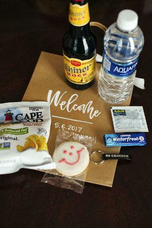 "When couples choose ""welcome gifts"" or wedding favors, many are focusing on items that relate directly to their history and interests, as seen in this ""welcome bag"" containing a keychain from a couple's college, a cookie from a restaurant chain the bride remembered from her childhood and a bottle of the groom's favorite beer, among other items."