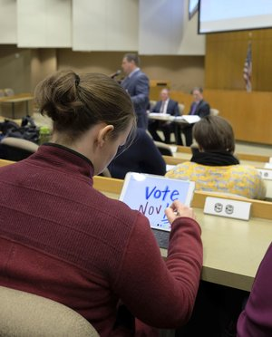 "Kathleen Lehman, a University of Arkansas faculty member at Mullins Library, doodles as UA spokesman Mark Rushing and others answer questions Thursday about implementation of a new law allowing licensed individuals to carry guns on campus legally. Her doodle said ""Vote Nov '18."""