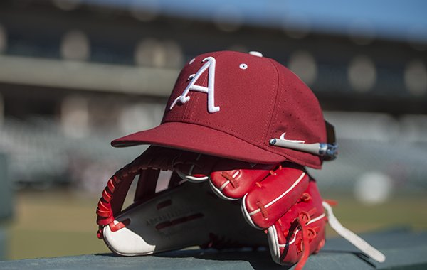 An Arkansas hat and glove sit at Baum Stadium during practice Saturday, Jan. 27, 2018, in Fayetteville.
