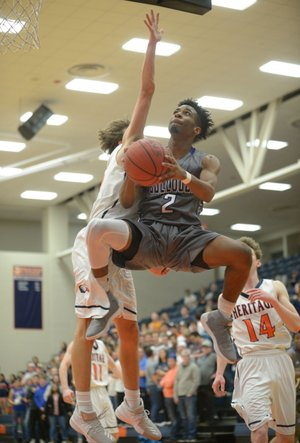 Fayetteville's Jon Conley (2) goes up and under Rogers Heritage's Logan Clines (left) on Tuesday at War Eagle Arena in Rogers. Visit nwadg.com/photos for more photos from the game.