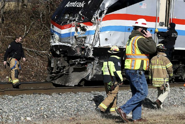 responders-walk-past-the-damaged-lead-engine-of-an-amtrak-train-that-crashed-into-a-garbage-truck-wednesday-morning-in-crozet-va