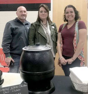 Photo by Sally Carroll Todd Daugherty (left) helped his wife, Janie Daugherty (center) and Summer Shafer as they served loaded white chicken chili potatoes at the International Food Fest Friday night. The group represented OPAA, which is the food service company for the McDonald County School District.