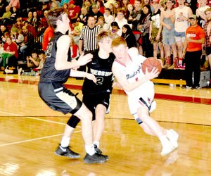 RICK PECK/SPECIAL TO MCDONALD COUNTY PRESS McDonald County's Blake Gravette drives around Neosho's Brady Wise (2) and A.C. Marion (22) during the Mustangs 50-44 win on Jan. 26 at MCHS.