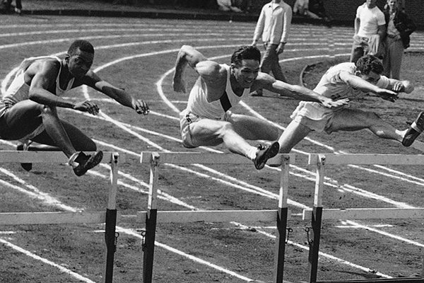 Clyde Scott, center, of Arkansas clears first hurdle in preliminary heat of 110-meter high hurdle event at NCAA meet in Minneapolis, June 18, 1948, before going on to win and set a record of 14 seconds flat. (AP Photo/Chet Magnuson)