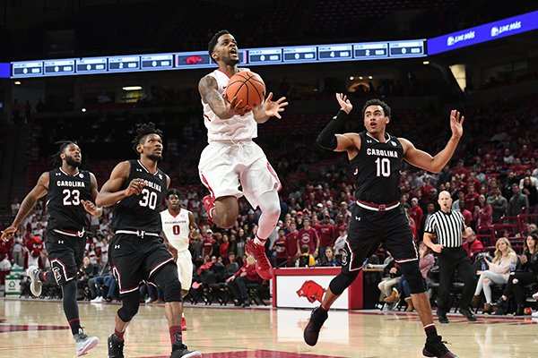 Arkansas' Daryl Macon goes up for a shot in front of South Carolina's Chris Silva (30) and Jutin Minaya (10) during a game Tuesday, Feb. 6, 2018, in Fayetteville.