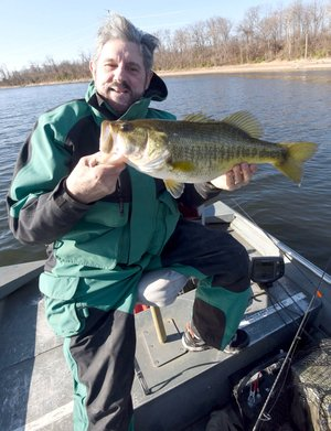 Westside Eagle Observer/FLIP PUTTHOFF Russ Tonkinson of Rogers shows a Swepco Lake largemouth bass he caught Dec. 13 2017 on a plastic worm. The 500-acre lake west of Gentry is a wintertime fishing destination because the water is warm all year.