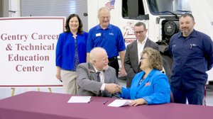 Westside Eagle Observer/RANDY MOLL Blake Robertson, president of Northwest Technical Institute, shakes hands with Terrie Metz, superintendent of the Gentry School District, on Jan. 31 after signing an agreement to offer college credit to graduating Gentry High School students who complete the course of study offered at the school in medium- and heavy-duty truck maintenance and repair. Standing behind Robertson and Metz were Christie Toland, assistant superintendent of Gentry Schools; Carl Desens, NTI instructor and department chair; Brae Harper, principal of Gentry High School Conversion Charter; and Tyson Sontag, instructor for the Gentry diesel mechanic courses taught in the new Gentry Career Education Center.